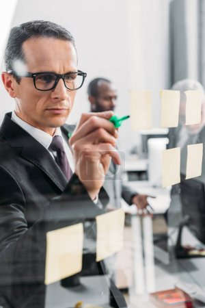 selective focus of businessman making notes in office