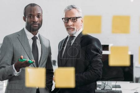 Photo for Selective focus of multicultural businessmen looking at notes during meeting in office - Royalty Free Image