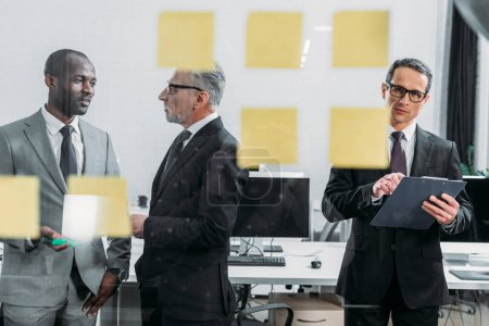 businessman with notepad looking at sticky notes while multicultural colleagues having discussion in office