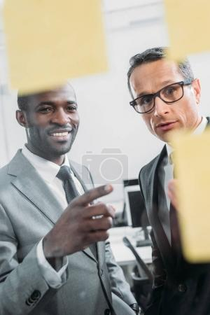 multiethnic businessmen looking at sticky notes on meeting in office