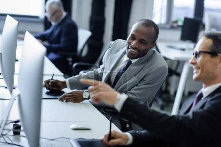 Photo for Selective focus of multicultural businessmen having conversation at workplace in office - Royalty Free Image