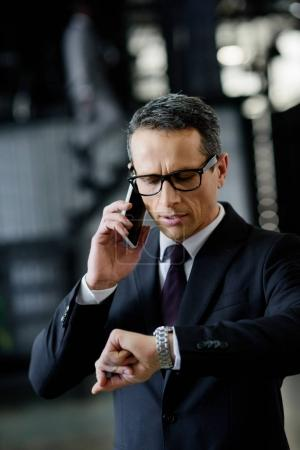portrait of businessman checking time while talking on smartphone