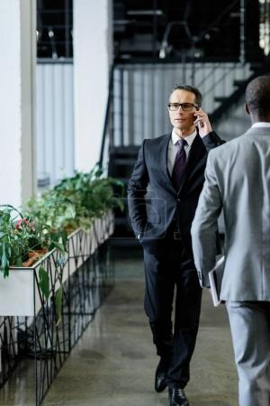 Photo for Confident businessman talking on smartphone while walking in office - Royalty Free Image