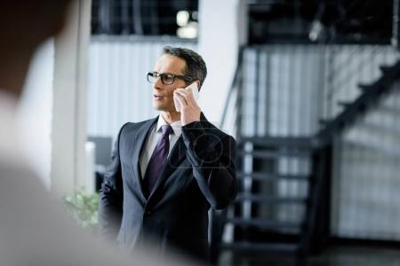 Photo for Businessman in eyeglasses talking on smartphone in office - Royalty Free Image