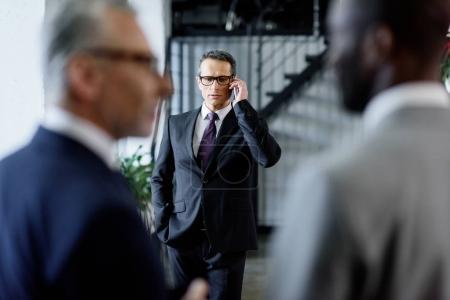Photo pour Mise au point sélective d'homme d'affaires, parler sur smartphone au bureau - image libre de droit