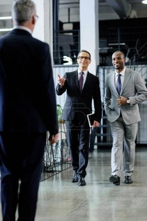 multiethnic smiling businessmen in suits walking in office