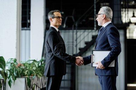 Foto de Vista lateral de colegas de negocios de alto nivel dándose la mano - Imagen libre de derechos