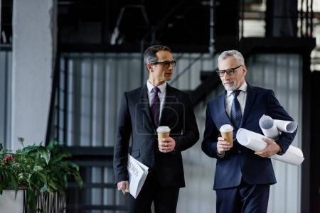 Photo for Portrait of businessmen with coffee to go in hands walking in office - Royalty Free Image