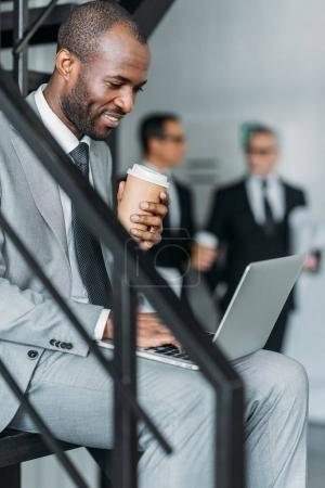 selective focus of smiling african american with coffee to go businessman working on laptop