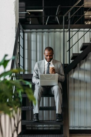 african american businessman with coffee to go using laptop while sitting on stairs