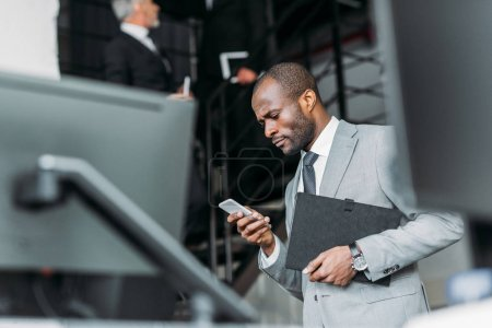 Photo for Selective focus of african american businessman with documents using smartphone - Royalty Free Image