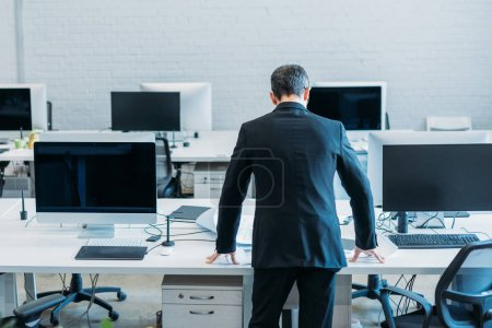 back view of businessman standing at workplace in office