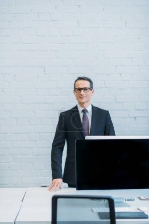 Photo pour Portrait d'un homme d'affaires souriant regardant une caméra sur le lieu de travail au bureau - image libre de droit