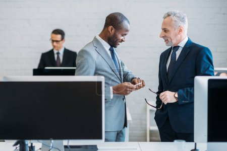 selective focus of multiracial business colleagues having conversation at workplace in office