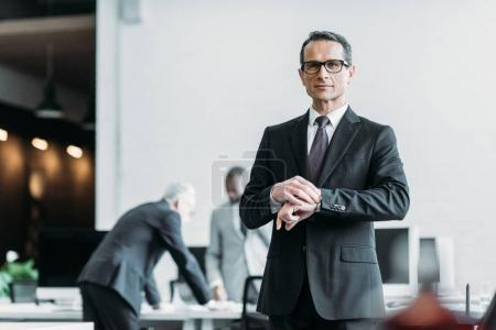 selective focus of businessman in eyeglasses checking time in office