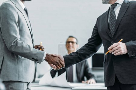 partial view of multiehtnic business colleagues shaking hands in office