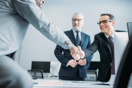 Photo for Partial view of multiehtnic business colleagues shaking hands in office - Royalty Free Image