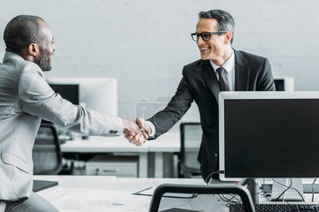 side view of multiehtnic business colleagues shaking hands in office