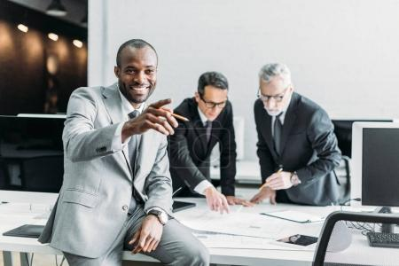 smiling african american businessman pointing away while business colleagues discussing work in office