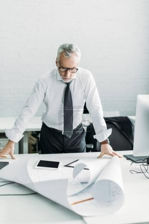 portrait of focused architect working with blueprints in office