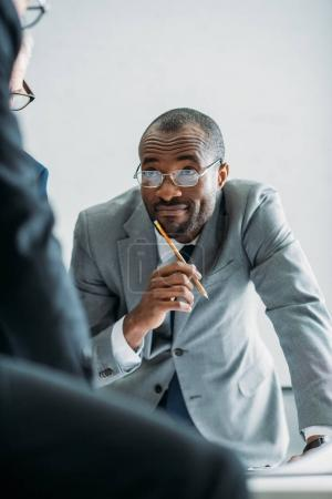 partial view of smiling african american businessman looking at colleagues during meeting in office