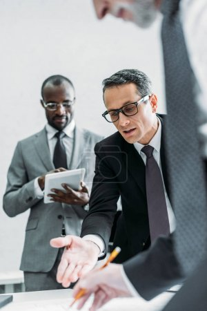 Photo for Partial view of multicultural businessmen discussing new plan on meeting in office - Royalty Free Image