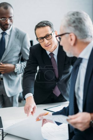 selective focus of multicultural businessman discussing new strategy in office