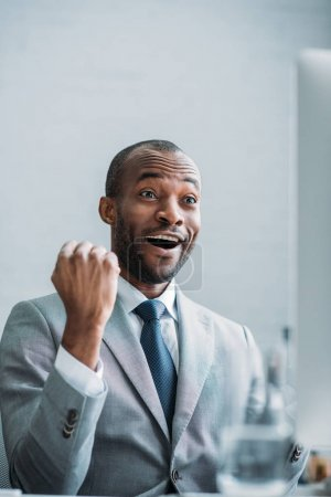 portrait of excited african american businessman at workplace in office