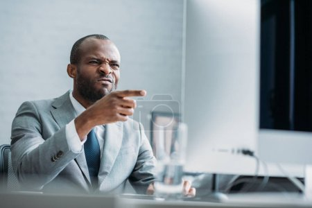 Photo for Portrait of african american businessman pointing at computer screen at workplace - Royalty Free Image