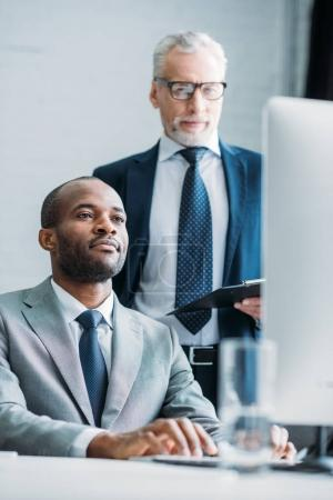 multiethnic business colleagues looking at computer screen at workplace in office