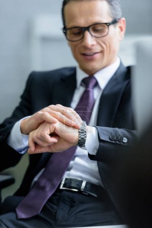 selective focus of smiling businessman checking time