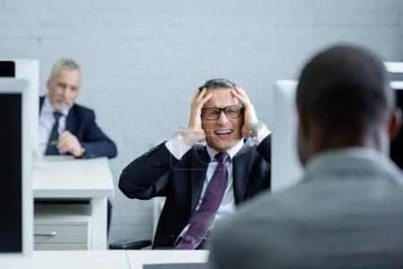 selective focus of stressed businessman at workplace in office