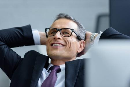 Photo for Portrait of cheerful businessman in eyeglasses with hands behind head - Royalty Free Image