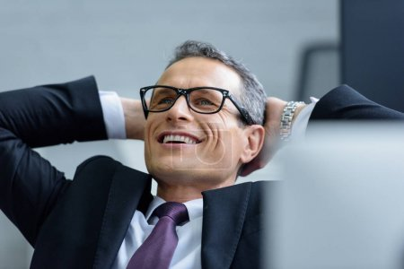 portrait of cheerful businessman in eyeglasses with hands behind head