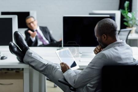 selective focus of african american businessman using tablet at workplace in office