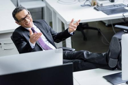 cheerful businessman in eyeglasses sitting at workplace in office