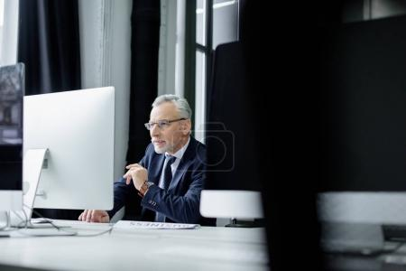 Photo for Selective focus of senior businessman working on computer in office - Royalty Free Image