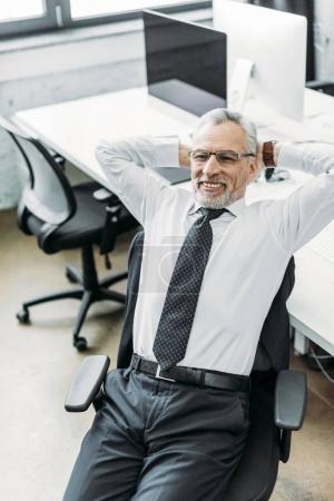 Photo pour Portrait d'une homme d'affaires senior souriant avec les mains derrière la tête dans le Bureau - image libre de droit