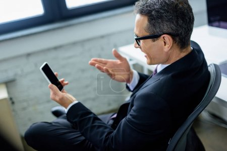 side view of smiling businessman using smartphone