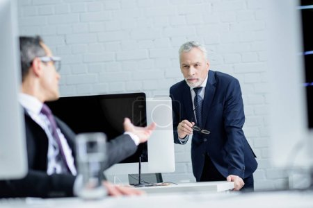 selective focus of business colleagues having conversation during work in office