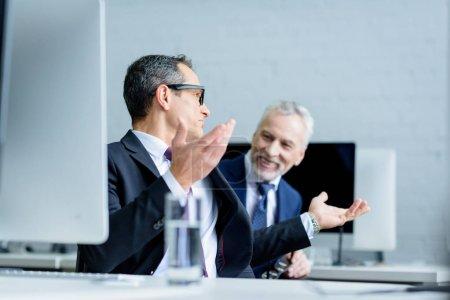 Photo pour Les collègues de travail ayant la conversation au cours de travaillent au bureau - image libre de droit