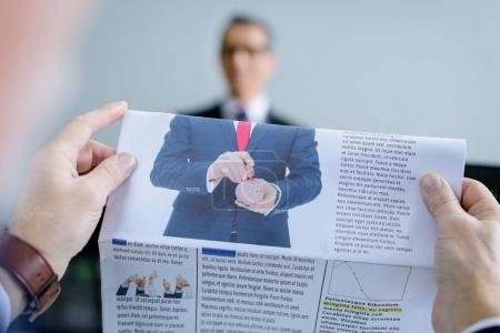 selective focus of businessman with newspaper and colleague