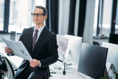 portrait of businessman with newspaper sitting on table in office