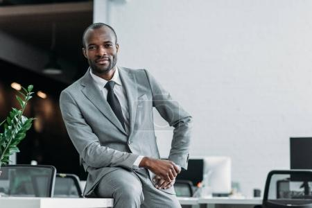 Photo for African american businessman sitting on table in office - Royalty Free Image