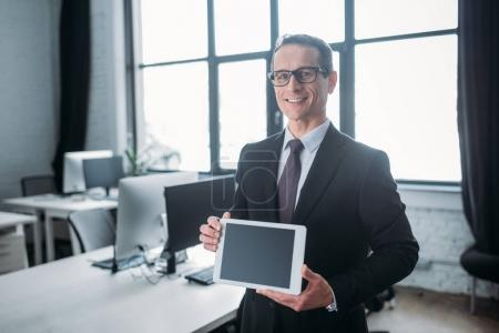 portrait of smiling businessman showing tablet with blank screen in hands in office