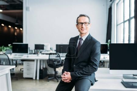 smiling businessman in eyeglasses sitting on table in office