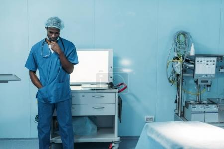 sad african american doctor standing in operating room