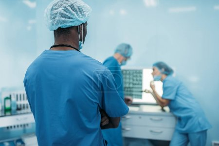 vue arrière des médecins multiculturelles en regardant patients aux rayons x