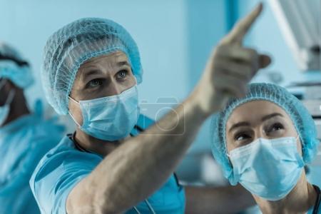 Photo pour Médecin pointant sur quelque chose dans la salle d'opération - image libre de droit
