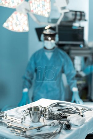 Photo for Surgeon looking at camera in operating room with tools on foreground - Royalty Free Image